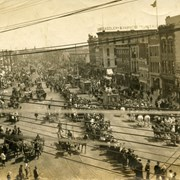 Cover image of Aerial view, steet scene, a crowd gathers to watch a circus riding into town, cable car tracks are visible in the street, horse drawn carriages pass by, some watch from rooftops